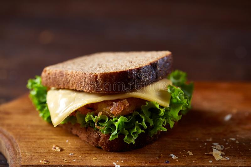 Tasty and fresh sandwiches on cutting board over a dark wooden background, close-up stock photography