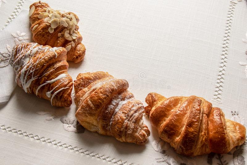 Freshly croissants with almonds,  powdered sugar on a table with napkins and tablecloth, closeup, top view. Tasty freshly  baked croissants with almonds stock photos