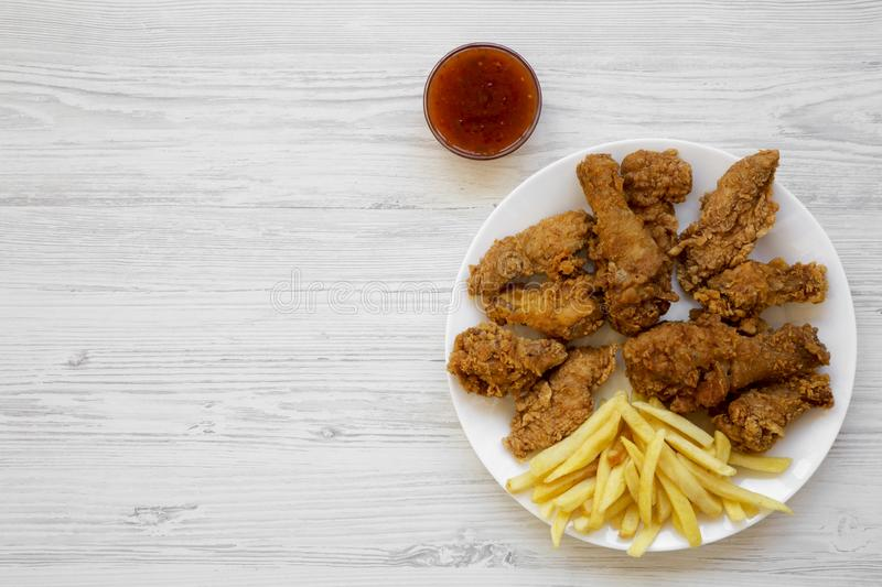 Tasty fried chicken legs, spicy wings, French fries, chicken tenders and sauce on white plate over white wooden background, top. View. Flat lay, overhead, from stock images