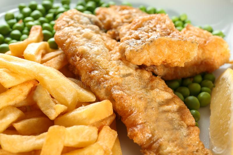 Tasty fried fish and chips on plate, stock photo