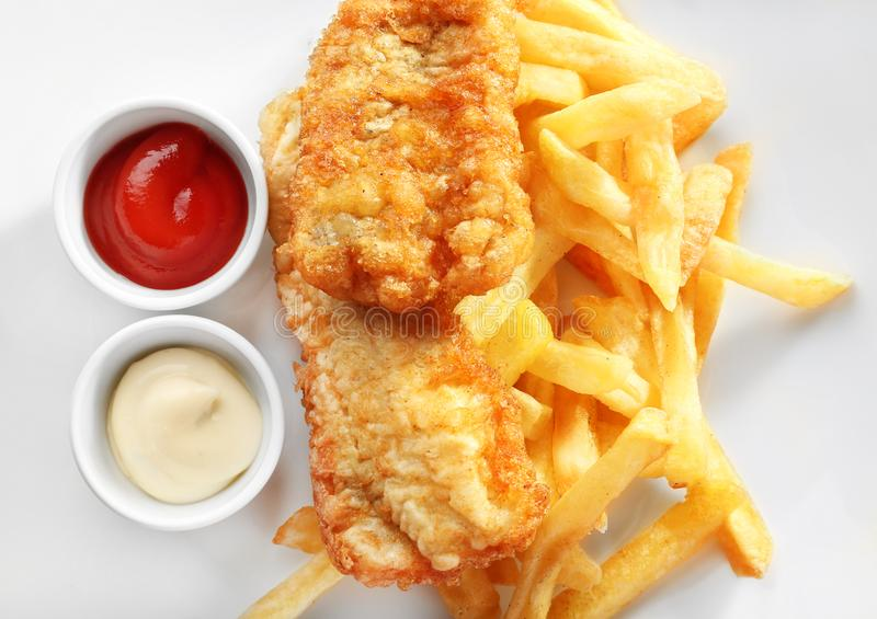 Tasty fried fish, chips and sauces on plate royalty free stock image