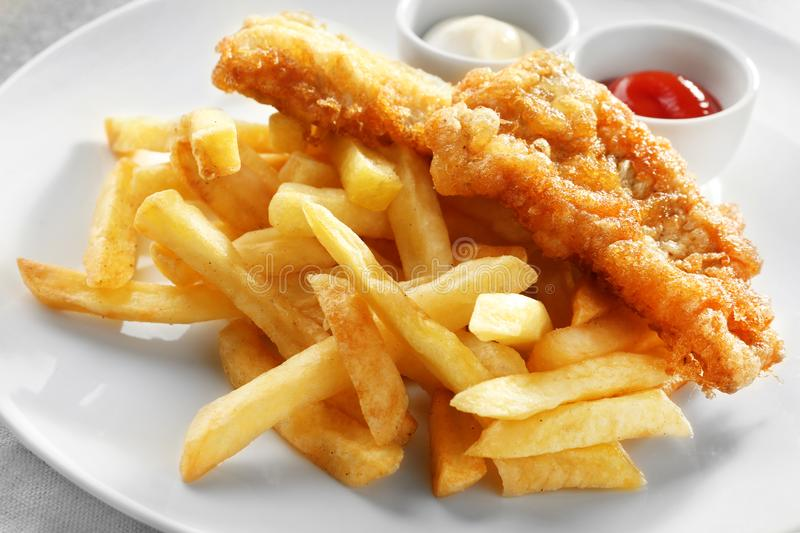 Tasty fried fish, chips and sauces on plate royalty free stock photography