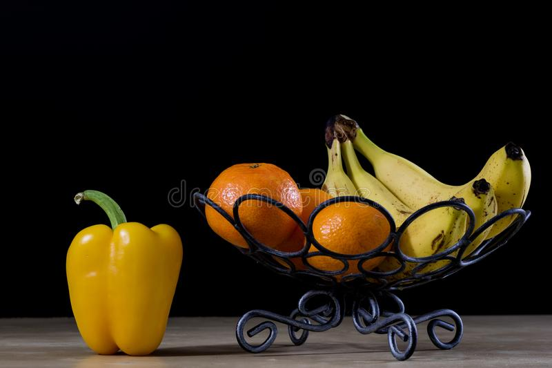 Tasty fruits in a metal basket. Wire basket with fruits on a woo. Den table. Black background stock photo