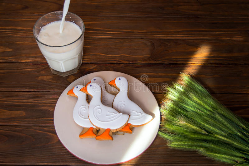 Tasty gingerbread suck shaped cookies on a plate with glass of milk and with ear of wheat on a wooden background royalty free stock photo