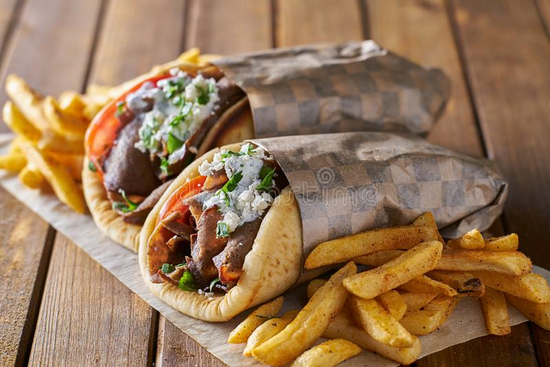 Tasty greek gyros with fries with feta cheese and tzattziki sauce stock photography