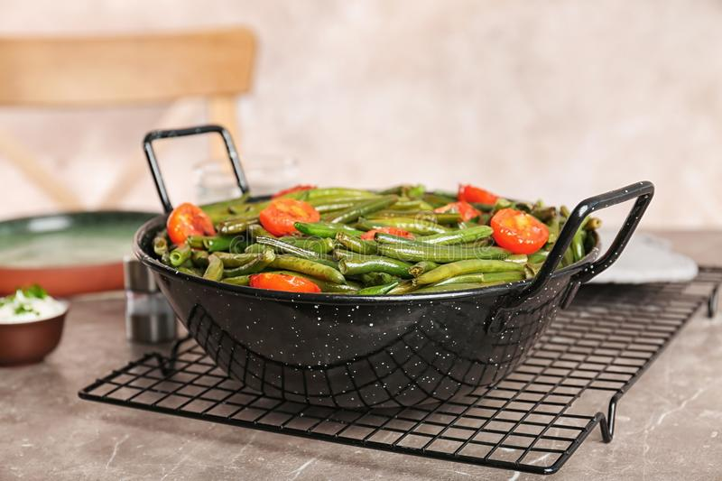 Tasty green beans with cherry tomatoes in serving pan. On table royalty free stock photo
