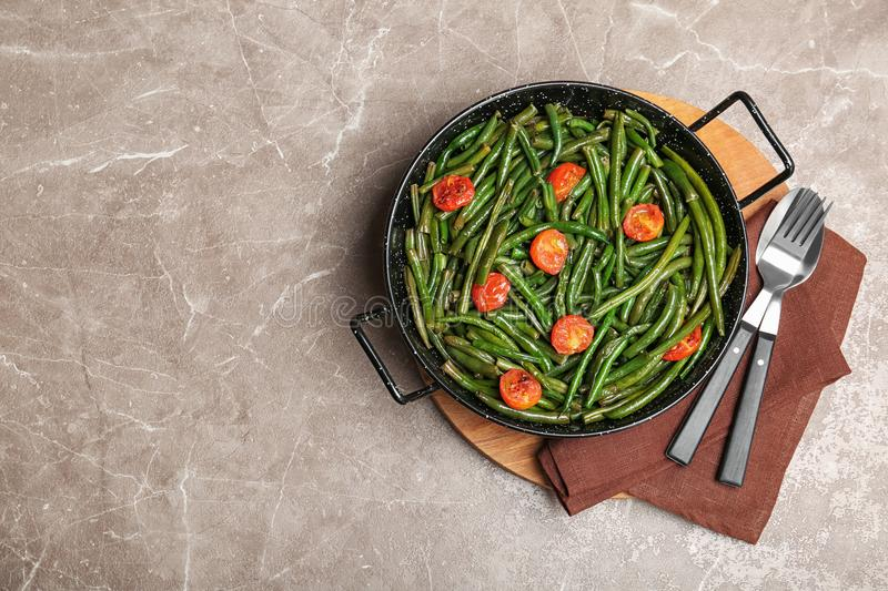 Tasty green beans with cherry tomatoes in serving pan. On table, top view royalty free stock photography