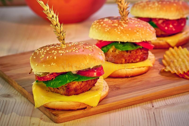 Tasty grilled beef burgers with lettuce, tomato, cheese and mayonnaise on rustic wooden board. Home made gamburgers. Fast food. stock photography