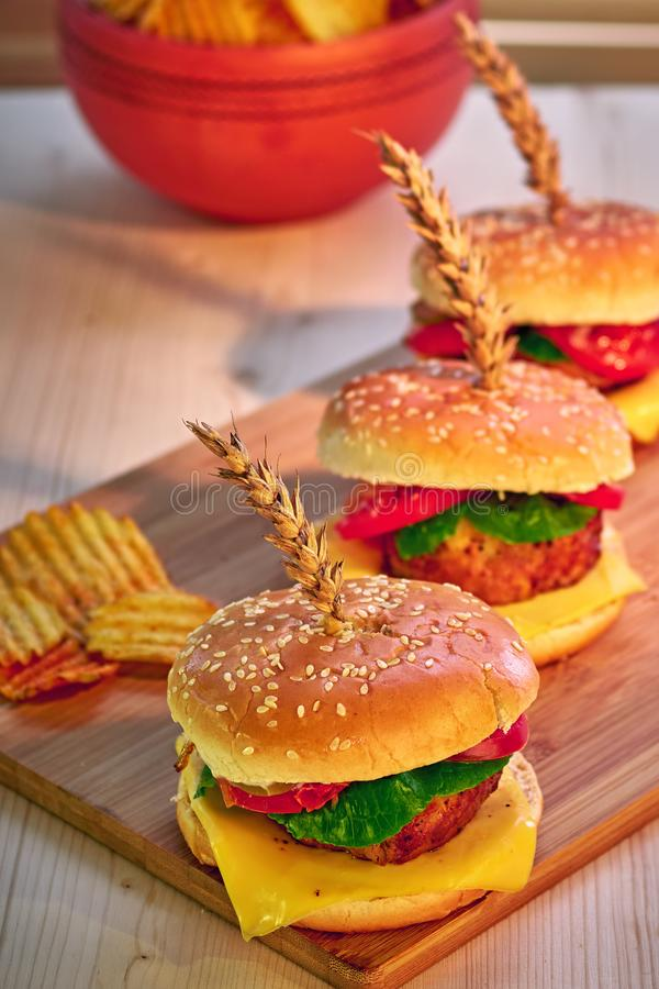 Tasty grilled beef burgers with lettuce, tomato, cheese and mayonnaise on rustic wooden board. Home made gamburgers. Fast food. royalty free stock image