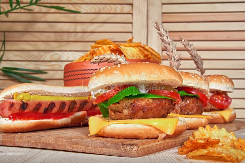 Tasty grilled beef burgers with lettuce, tomato, cheese and mayonnaise on rustic wooden board. Home made gamburgers. royalty free stock photo