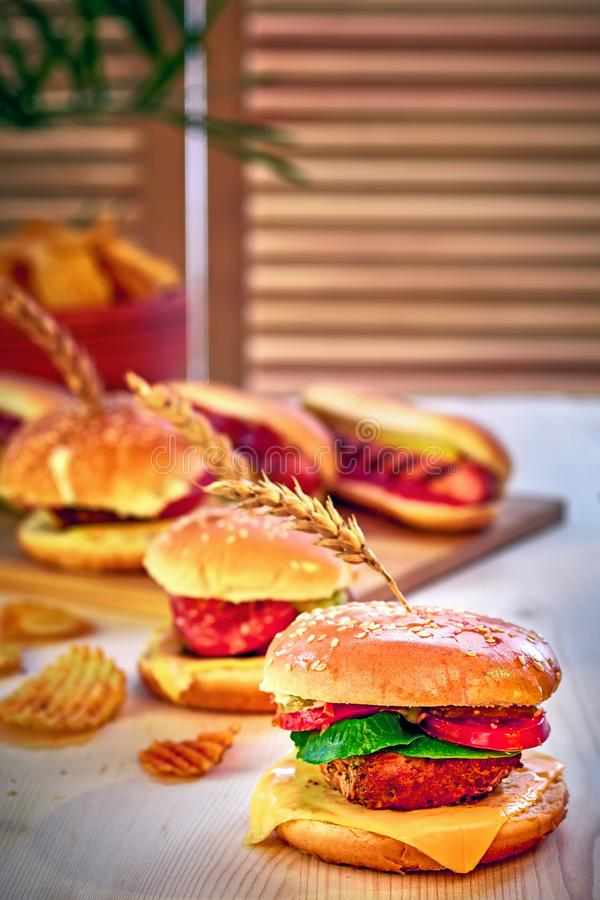Tasty grilled beef burgers with lettuce, tomato, cheese and mayonnaise on rustic wooden table. Home made gamburgers, copy space. stock photography