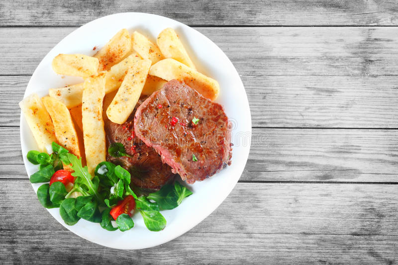 Tasty Grilled Beef with Fries and Herbs on Plate stock photo