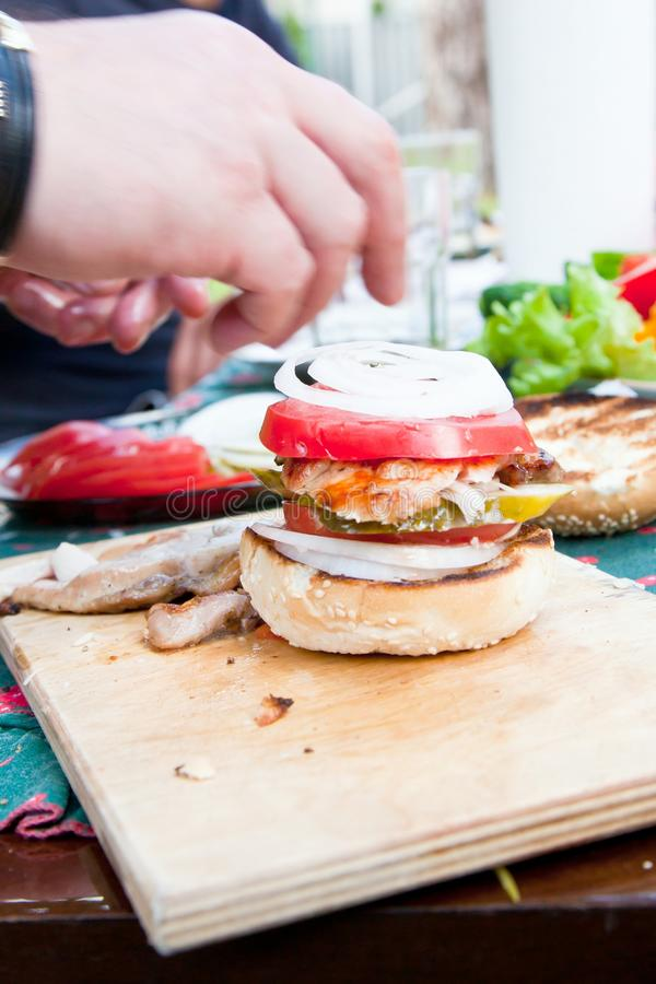 Tasty grilled chicken burger with lettuce and mayonnaise served on on a rustic wooden plate on table stock image