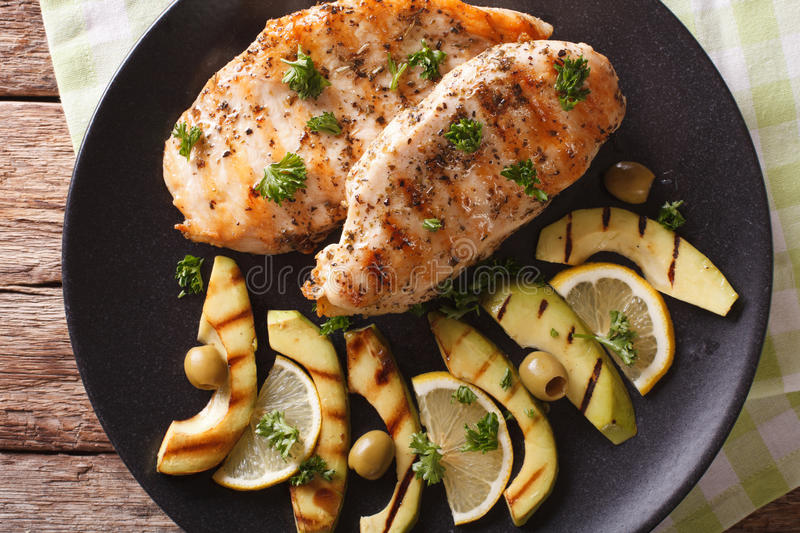 Tasty grilled chicken fillet with avocado, lemon and olive close royalty free stock image