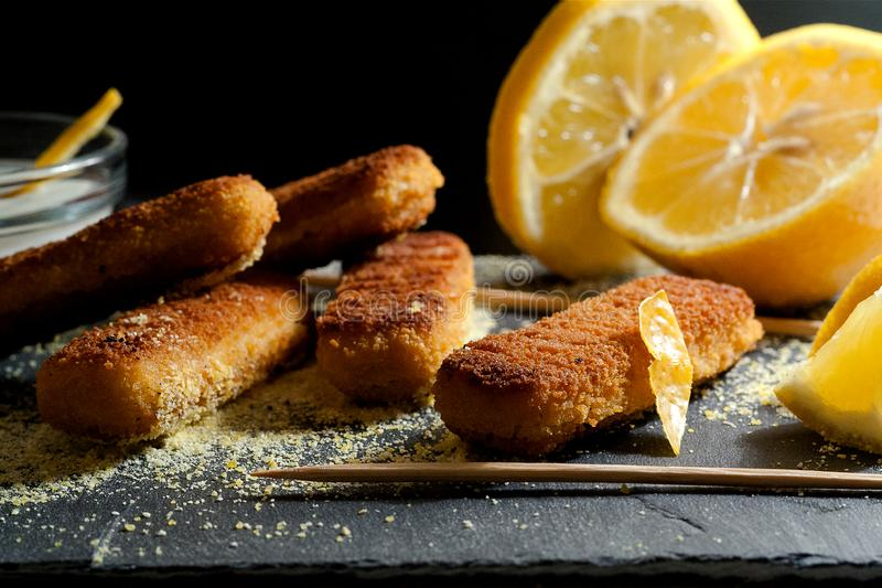 Crispy and tasty fish fungers with lemon and garlic dill sauce, served on stone plate royalty free stock photography