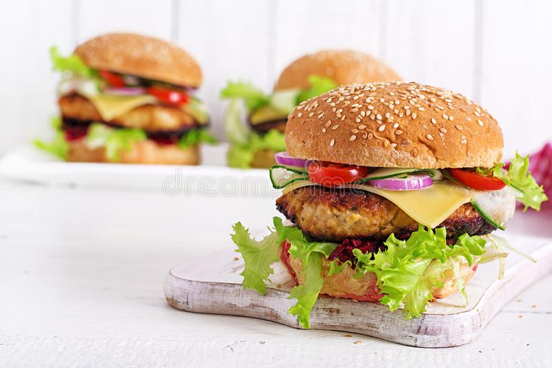 Tasty grilled homemade hamburger with burger chicken, tomato, cheese. Cucumber, lettuce and beetroot. Sandwich. Lunch stock photo