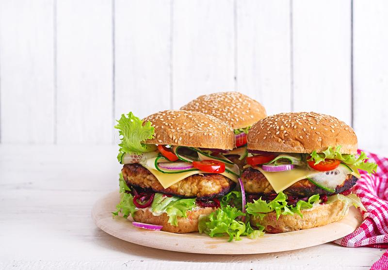 Tasty grilled homemade hamburger with burger chicken, tomato, cheese. Cucumber, lettuce and beetroot. Sandwich. Lunch royalty free stock images