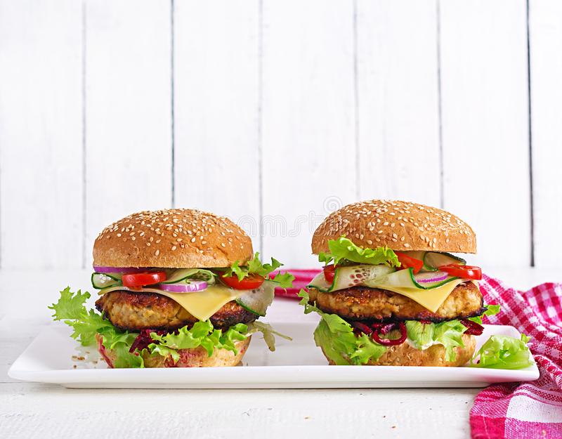Tasty grilled homemade hamburger with burger chicken, tomato, cheese. Cucumber, lettuce and beetroot. Sandwich. Lunch stock image