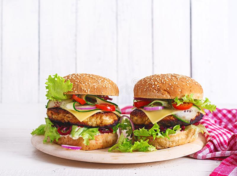 Tasty grilled homemade hamburger with burger chicken, tomato, cheese. Cucumber, lettuce and beetroot. Sandwich. Lunch stock photos