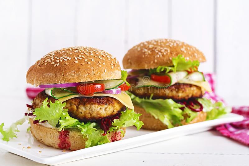 Tasty grilled homemade hamburger with burger chicken, tomato, cheese. Cucumber, lettuce and beetroot. Sandwich. Lunch royalty free stock photography