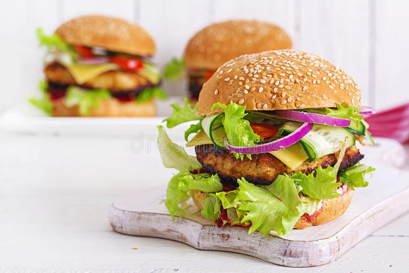 Tasty grilled homemade hamburger with burger chicken, tomato, cheese. Cucumber, lettuce and beetroot. Sandwich. Lunch stock images