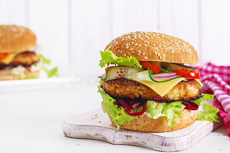 Tasty grilled homemade hamburger with burger chicken, tomato, cheese. Cucumber, lettuce and beetroot. Sandwich. Lunch royalty free stock photo
