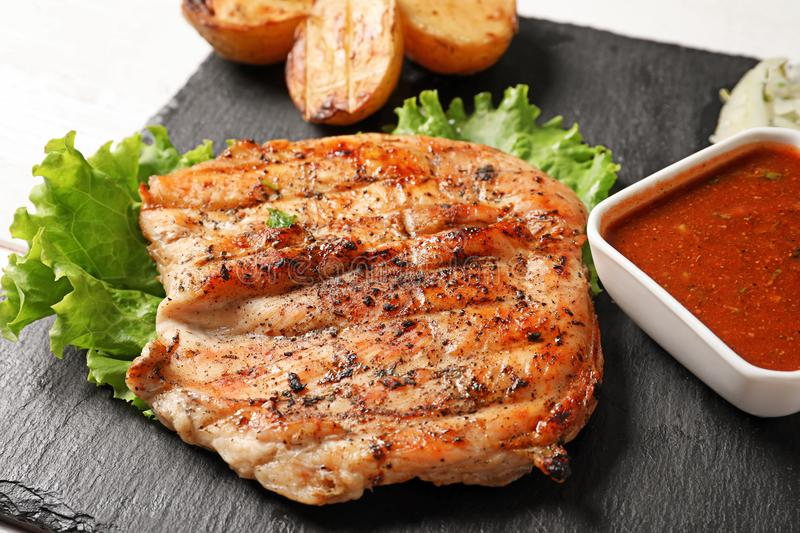 Tasty grilled meat and sauce served on slate plate, closeup royalty free stock photo