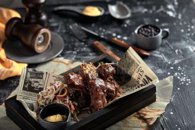 Tasty grilled ribs seasoned with spicy sauce and chopped fresh vegetables on an old rustic wooden cutting board with royalty free stock photography