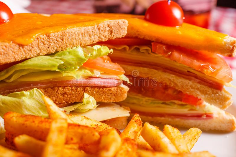 Tasty grilled sandwich in the restaurant. Club sandwich with ham, tomato, cheese and lettuce. Served with French fries stock photos