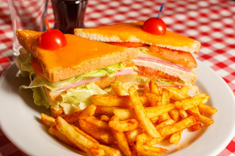 Tasty grilled sandwich in the restaurant. Club sandwich with ham, tomato, cheese and lettuce. Served with French fries stock images