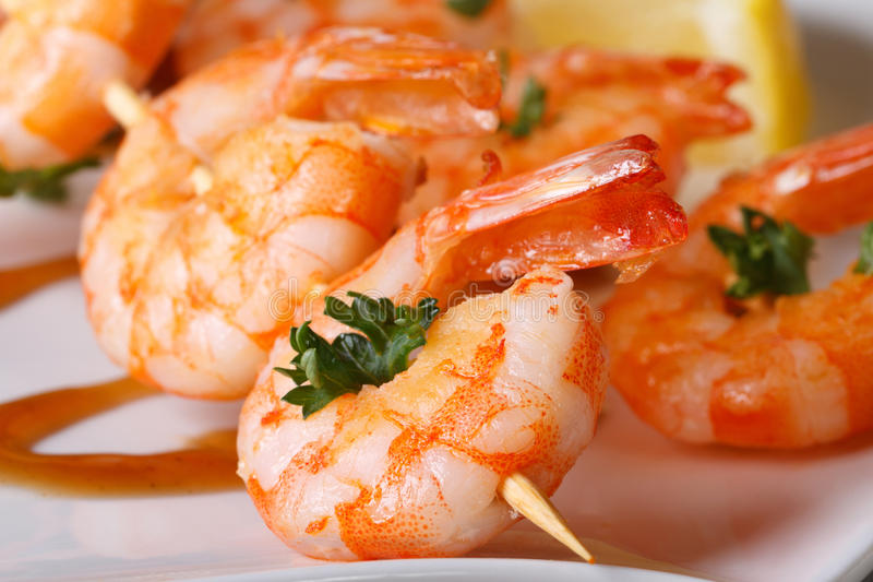 Tasty grilled shrimp on wooden skewers macro with sauce stock photo