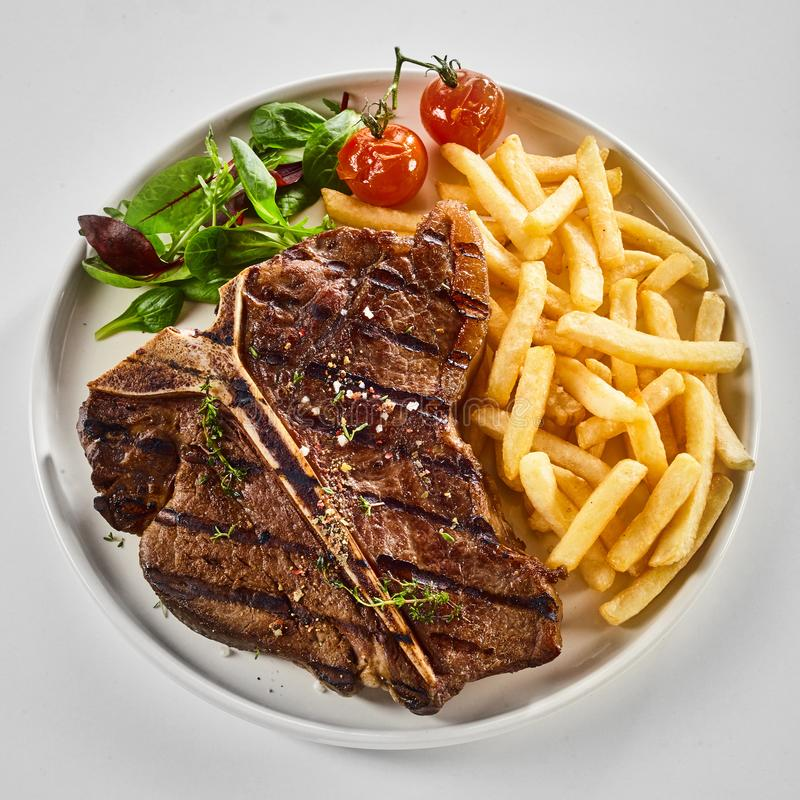 Tasty grilled T-bone steak with fried potato chips royalty free stock photography