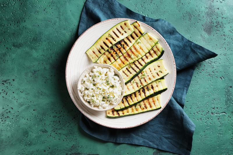Tasty grilled zucchini with cottage cheese on plate stock photo