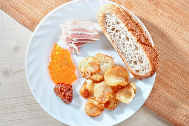 Tasty harmful food. Greasy fried. Potatoes, bacon, red caviar, spicy sauce and white bread on a white plate. Snacking royalty free stock image