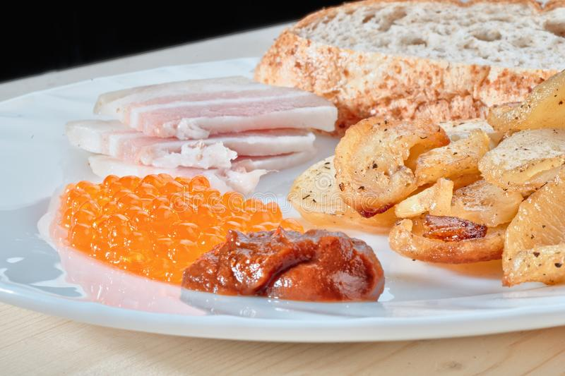 Tasty hazardous food. Greasy fried. Potatoes, bacon, red caviar, spicy sauce and white bread on a white plate. Russian snacking royalty free stock photos