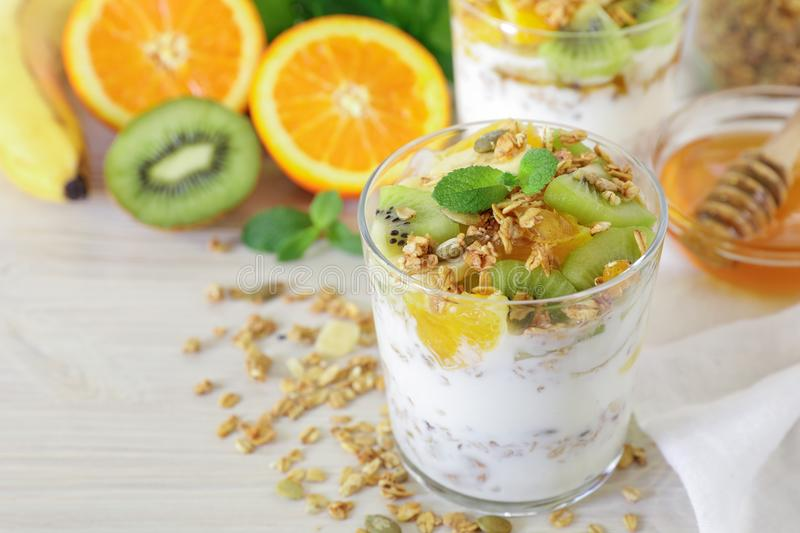 Tasty and healthy breakfast or snack: yogurt, granola and kiwi, orange, banana slices, honey, mint leaves on a white wooden backgr. Ound. Horizontal. Daylight royalty free stock images