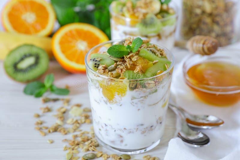 Tasty and healthy breakfast or snack: yogurt, granola and kiwi, orange, banana slices, honey, mint leaves on a white wooden backgr. Ound. Horizontal. Daylight royalty free stock photo