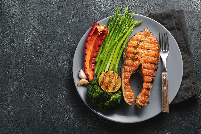 Tasty and healthy salmon steak with asparagus, broccoli and red pepper on a gray plate. Diet food on a dark background with copy stock image