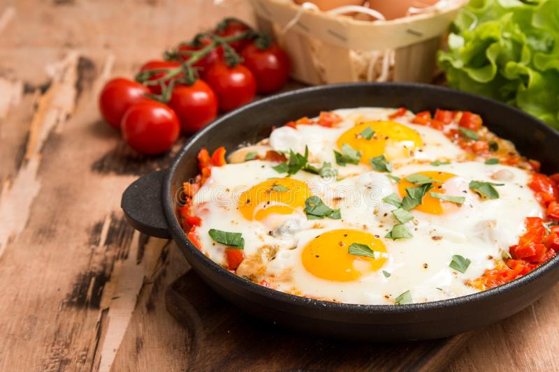 Tasty and Healthy Shakshuka in a Frying Pan. Fried eggs with tom. Atoes, bell pepper, vegetables and herbs. Middle eastern traditional dish stock photos