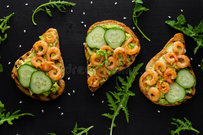 Tasty healthy snack with avocado toasts, cucumber and shrimps on black background. stock photography
