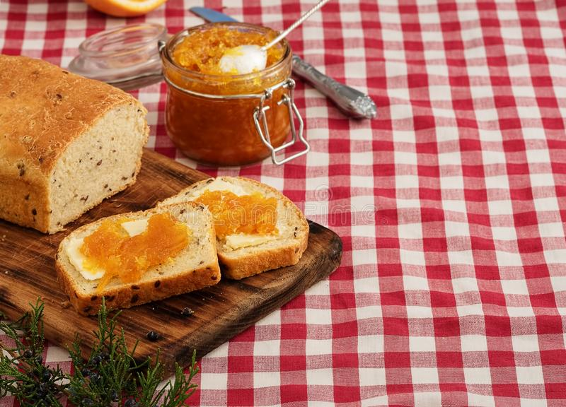 Tasty homemade bread on a wooden board. Slices of bread with butter and jam. A can of orange jam is nearby. The concept of a stock photos