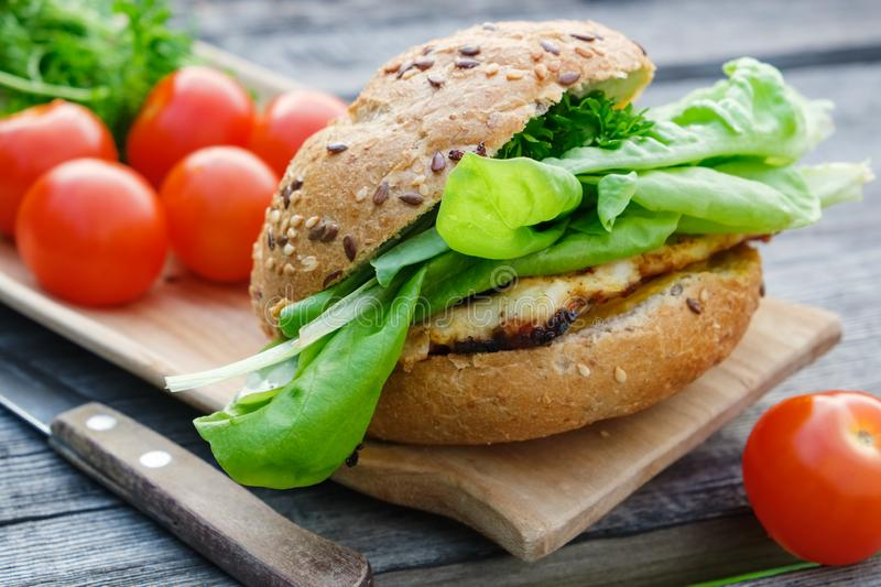Tasty homemade burger with meat, lettuce, tomatoes, bun on picnic table outdoors stock photos