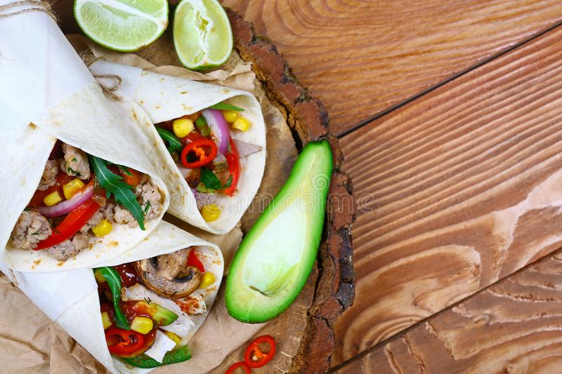 Tasty homemade burrito with vegetables and beef on a paper. mexican food royalty free stock photos