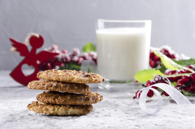 Tasty homemade cookies and glass of milk, traditional Christmas snack on the grey table. Christmas ornaments and food royalty free stock photos