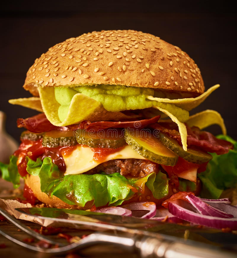 Tasty hоmemade delicious burger with guacamole and nachos on a stock image