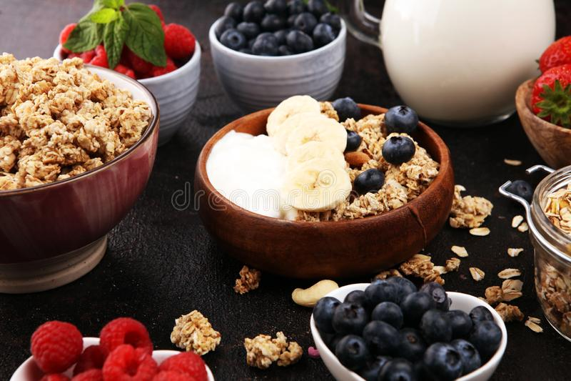 Tasty homemade granola served on table. Healthy breakfast with a bowl of oatmeal with banana, blueberries, strawberries and royalty free stock photos