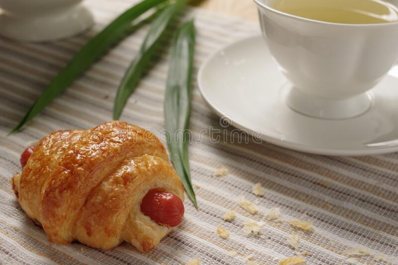 Tasty homemade homemade hotdog croissant with earl grey in the afternoon tea. stock photo