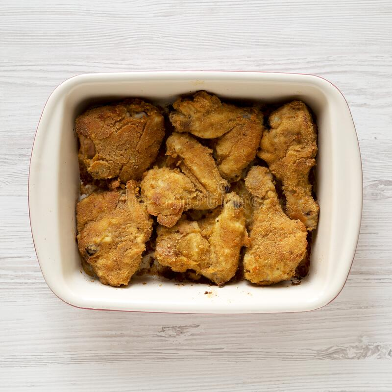 Tasty homemade oven baked fried chicken in a dish over white wooden background, top view. Flat lay, overhead, from above.  stock image
