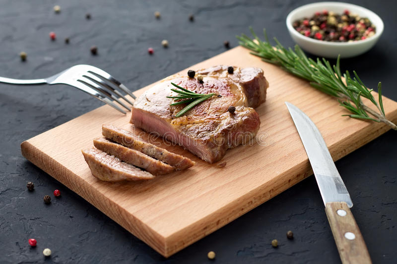 Tasty homemade well-done steak on wooden cutting board with fork and knife on stone background. stock photos