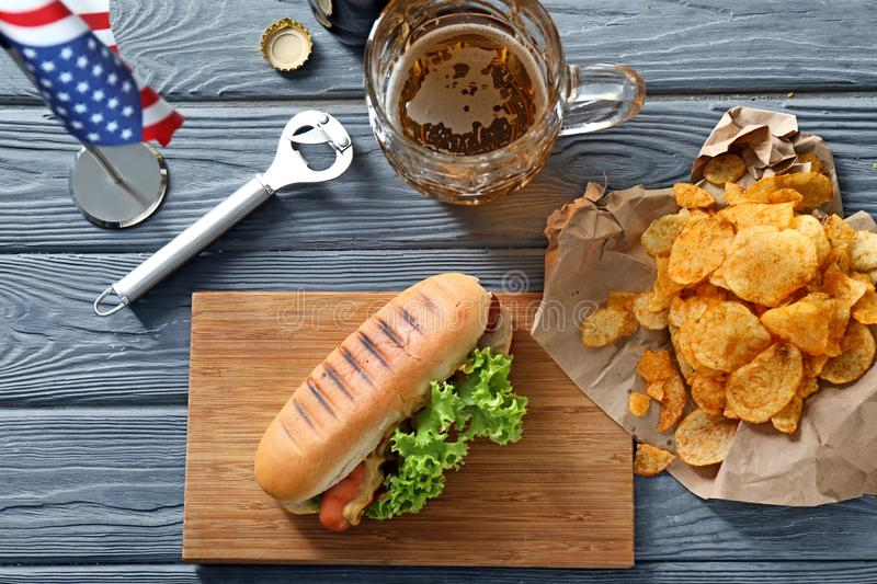 Tasty hot dog with glass mug of beer and potato chips on wooden table stock photo
